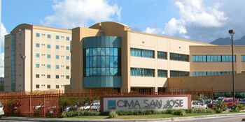 Picture of CIMA Hospital – San José, Costa Rica, a tall, large 3-story building, tan in color, with a large entrance sign saying CIMA -  San José.