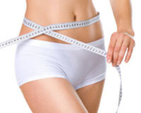 Picture of a woman holding a measure tape to her hips after liposculpture